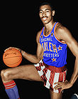Man in a Harlem Globetrotters uniform is on one knee and holding a basketball.