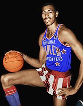 A black basketball player, wearing red and white pants and blue jersey and holding a basketball, stands with his right leg up