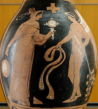 Genius (mythology) - Winged genius facing a woman with a tambourine and mirror, from southern Italy, about 320 BC.
