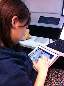 woman playing candy crush saga on an ipad