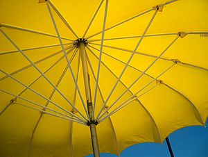 Yellow beach umbrella in the summer sun.
