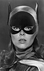 A black-and-white portrait of Yvonne Craig as Batgirl, wearing a mask that covers the top half of her face, though with eyes and nose exposed.  She is also wearing a hood that has bat-like ears extending up on each side of her head.
