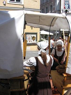 Women in Estonia - Two modern-day Estonian women at work while wearing traditional costume.