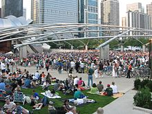 A large number of people are seated on the grass facing a bandshell with an even larger crowd across a wide sidewalk. The bandshell is framed by shiny curved metal and a trellis is over the larger crowd. Skyscrapers are in the background.