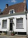 foto van Laag huisje onder zadeldak met stoep, rechte kroonlijst, gepleisterde gevel