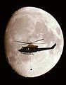 A Griffin Helicopter, with an underslung load, shown in silhouette against a full moon.jpg