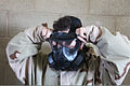 A U.S. Marine with the 9th Communication Battalion breaks the seal on his M50 gas mask during a chemical, biological, radiological and nuclear defense confidence course July 8, 2011, at Camp Pendleton, Calif 110708-M-BT412-041.jpg