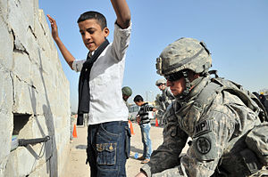 History of Iraq - U.S. Army soldier searches an Iraqi boy, March 2011.