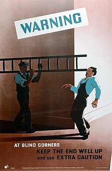 A man carrying a ladder around a corner accidentally strikes the eye of a man approaching around the corner from the right side of the image, as shown by little dashes. They wear overalls suggesting a workplace uniform. Text warns to use caution at corners.