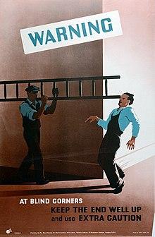 Un homme portant une échelle dans un coin frappe accidentellement l'œil d'un homme qui s'approche du coin à droite de l'image, comme le montrent de petits tirets.  Ils portent des combinaisons suggérant un uniforme de travail.  Le texte avertit d'être prudent dans les coins.