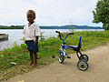 A small boy in a school uniform stands next to his tricycle. (10663272896).jpg