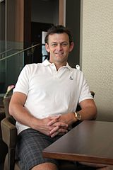 Adam Gilchrist sitting in a chair smiling, leaning on a desk.