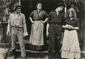 Florence Lawrence - Margie (played by Florence Lawrence, far right) is loved by both Rob (Owen Moore, on the left) and Orin (Gladden James, right) in this publicity still from the 1912 Victor production After All. Margie's widowed mother (played by Victory Bateman) stands on the stoop.