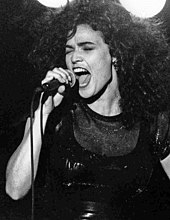 Black and white image of a woman with her eyes closed and mouth open, holding a microphone.