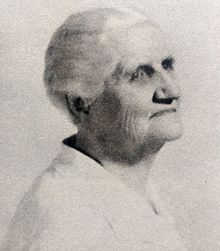 Black and white sideview image of an aging woman with white hair pulled back. She is wearing a white blouse.