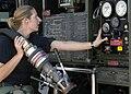 An airman rewinds a fuel hose after refueling an aircraft.jpg