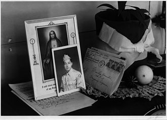 War Relocation Authority - A homemade planter and a doily beside a service portrait, a prayer, and a letter home. One of the few ways to earn permission to leave the camps was to enter military service.