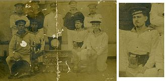 """Karl Artelt -  Karl Artelt on board the """"Gneisenau"""" 1912 (lower row, second from right and detail enlargement); the board between the sailors reads: Pumpenmeister Personal SMS """"Gneisenau"""", Amoij, China 1912 (master pump personnel SMS """"Gneisenau"""", Amoij, China 1912)"""