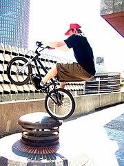 BMX-Fahrer springt mit Hinterrad an ein Hindernis. Diesen Trick nennt man Abubaca