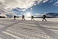 Backcountry campers ski along the road in Lower Geyser Basin at sunset (39607038962).jpg