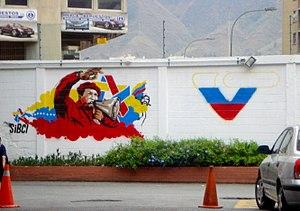 Bolivarian propaganda - A mural representing SiBCI sharing Chávez's message beside the VTV logo.