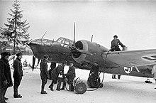 Un avión bombardero finlandés está siendo repostado a mano por seis militares en una base aérea en un lago helado.