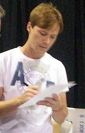 A fair haired young man wearing a white T-shirt, signing a piece of paper