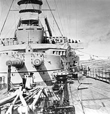Two long gun barrels jut out of a wide, round gun turret aboard a warship; the deck is covered in heavy chains, winches, and cranes