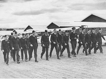 Fifteen men in dark military uniforms walking in front of biplanes and huts
