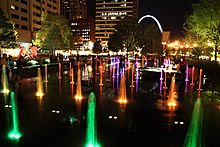 In this low aerial night shot, numerous fountains shoot water into the air, illuminated by colored lights.