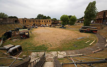 Wide view of the fort's interior, showing a semi-circular sandy area in which items of military equipment are standing. A row of brick buildings is visible at the rear.