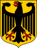 Coat of arms featuring a large black eagle with wings spread and beak open. The eagle is black, with red talons and beak, and is over a gold background.