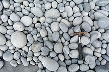 A rock hammer rests atop a variety of well-rounded gray cobbles.