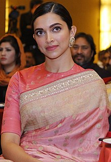 Deepika Padukone in a pink sari looking away from the camera