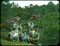 Eight young women in Kimonos, four in wooden boat on water, four on bank beside boat, two of them holding open parasols. (19950370935).jpg