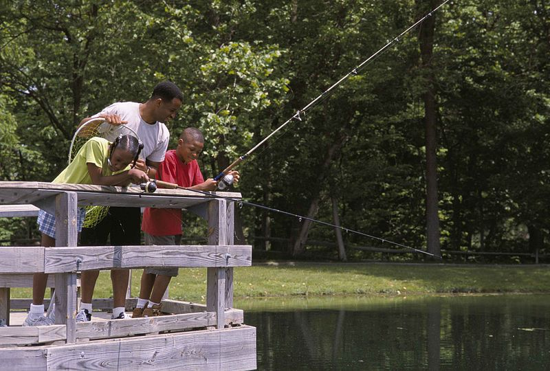 File:Family fishing from a bridge at a local pond.jpg