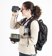 A Woman with a backpack holding a laser rangefinder, a handheld GPS and a Tablet computer.