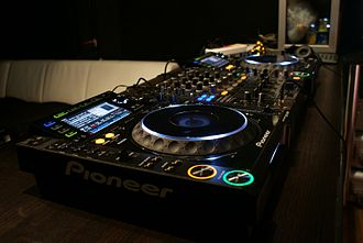 Pioneer DJ - The CDJ-2000, a CD player designed by Pioneer DJ. A DJM-800 mixer is also seen in the middle.