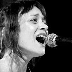 Black and white image of a woman singing into a microphone