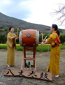 Two women wearing kimonos perform traditional Hachijō-daiko.