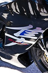 The side of the bodywork of a sport motorcycle with the legend Hayabusa superimposed on a Japanese character 隼.