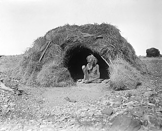 History of the Northern Territory - An Arrernte Man in a traditional hut in 1920.