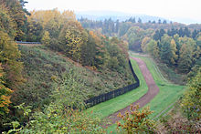 At the base of a wooded slope to the left, there is a black fence running into the distance, flanked on the right by a strip of closely cropped grass, then a strip of bare soil, then another strip of grass, and then a patrol road. Halfway up the wooded slope, a white cross is visible.