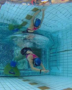 Underwater view of an underwater swimmer launching off the end of a pool.