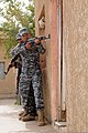 Iraqi police Sgt. Tawfiq Fadal Khaliaf points his AK-47 rifle at the ready before breaching a door with his fellow policemen during room entry and clearing procedures training at the Abu Risha Brigade 110719-A-FO214-268.jpg