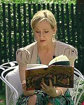 Une femme blonde aux cheveux attachés est assise en extérieur sur une chaise de jardin blanche. Elle est légèrement penchée en avant pour lire le livre qu'elle tient dans les mains
