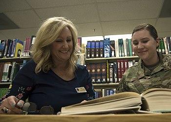 Дженнифер Крауэлл, пятьдесят шестая группа поддержки Squadron директор библиотеки, помогает Airman 1-го класса Zoie Кокс, 56-й истребительный авиаполк по связям с общественностью фотожурналиста, найти запись в книге 8 апреля 2019, на базе ВВС США Люк, штат Аризона.