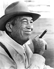 Un John Huston souriant, tenant un cigare