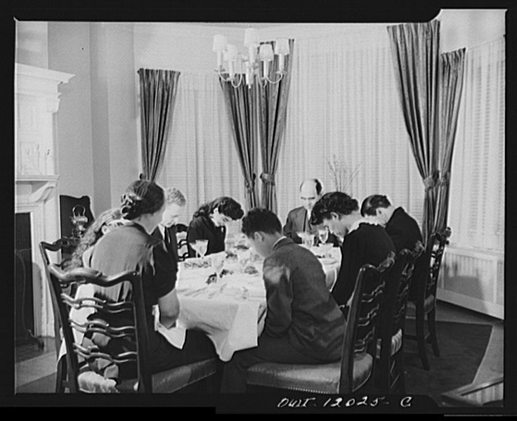 Dr. Mordica Johnson and family sitting around a food-laden table  saying grace before Thanksgiving dinner