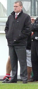 Karl Marginson, F.C. United's manager, stands at the side of a football pitch watching the game.